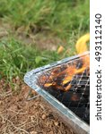 Small photo of Disposable barbecue alight on the grass
