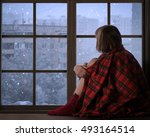 Small photo of Girl sits on the window sill of the window and looks at the falling snow. The concept of home comfort, season, solitude