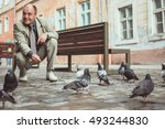 Man Feeding Pigeons In The Old...