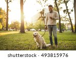 Stock photo man walking his dog and texting on a mobile phone 493815976
