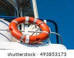 Bright orange lifebuoy on a white yacht side. Blue sky background