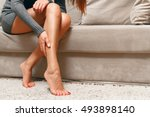 Small photo of Young woman sitting on the couch suffering from severe pain in the leg