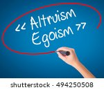 Small photo of Women Hand writing Altruism - Egoism with black marker on visual screen. Isolated on blue. Business, technology, internet concept. Stock Photo