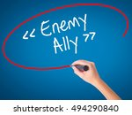 Small photo of Women Hand writing Enemy - Ally with black marker on visual screen. Isolated on blue. Business, technology, internet concept. Stock Photo