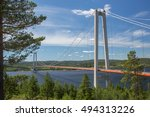 Hoga Kusten or High Coast Bridge from the north bank of the river Angermanalven in eastern Sweden. Trees in foreground and partly cloudy blue skies in the background.
