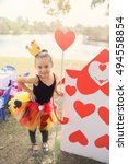 Small photo of cute girl with handmade red heart card with Alice in wonderland party theme, toning