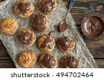 eclairs on wood background. | Shutterstock . vector #494702464