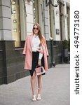 Stock photo young stylish beautiful woman walking in street wearing pink coat purse sunglasses white shirt 494773180