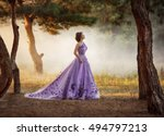 Small photo of Lady in a luxury lush purple dress . Fantastic shot. Fairytale princess is walking in the autumn forest. Fashionable toning.Creative computer colors.