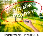 Small photo of Woman Hand Writing Altruism - Egoism on blank transparent board with a marker isolated over green field background. Stock Photo