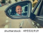 Happy handsome young business man driver in his car looking to the road side view mirror. Positive human face expression emotions. Safe trip journey driving concept - stock photo