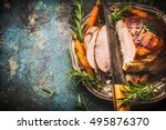 Small photo of Roasted pork ham with kitchen knife and roast vegetables on dark rustic background, top view, border
