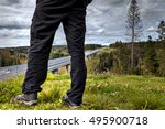 Close-up of man legs on the background of a highway viaduct crossing the forest in rural Russia. - stock photo