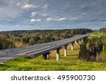 Steel bridge overpass on concrete supports, highway crosses Russian forest, sunny summer day. - stock photo