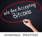 Small photo of Woman Hand Writing We Are Accepting Bitcoins on blank transparent board with a marker isolated over black background. Business concept. Stock Photo