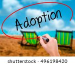 Small photo of Man Hand writing Adoption with black marker on visual screen. Isolated on sunbed on the beach. Business, technology, internet concept.
