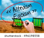 Small photo of Man Hand writing Altruism - Egoism with black marker on visual screen. Isolated on sunbed on the beach. Business, technology, internet concept. Stock Photo