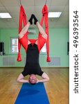 Small photo of Anti-gravity Yoga, man doing aero exercises with hammock in class, upside down