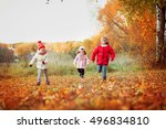 Small photo of three children, a boy and two girls, 4 and 6 years, the brothers and sisters in the autumn park near the river run one after the other