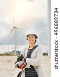 Small photo of smiling engineer woman crossing arms with safety helmet, gloves, glasses and ear muffs at wind turbine farm generating energy with air flow spinning blades. Clean renewable green wind power concept.