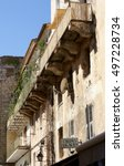 """Small photo of Old balcony at an ancient building in an alleyway of uptown Porto Vecchio, signpost for """"Crepes"""" and """"Glaces"""" (ice cream) at the lower image boarder; Porto Vecchio, Corsica, France; 10/09/2014"""
