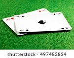 Small photo of Two aces on green felt casino table, ace of spades on top. Selective focus on the spade symbol