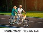 senior couple rides tandem bike.... | Shutterstock . vector #497539168