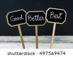Small photo of Business message Good, Better, Best written with chalk on wooden mini blackboard labels, defocused chalkboard and wood table in background