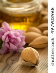 Small photo of Almond oil and almonds on an old wooden background, selective focus