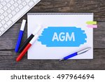 Small photo of Notebook with AGM Handwritten on wooden background and Modern Computer Keyboard. Top View Composition