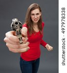 Small photo of furious young woman self-defending with an oversized hand gun in the foreground, expressing revenge, hate or accusation with a firearm