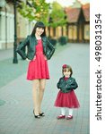 Small photo of Beautiful young mother and daughter dressed alike(3)