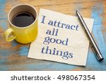 Small photo of I attract all good things - positive affirmation words - handwriting on a napkin with a cup of coffee