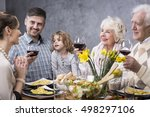Small photo of Multigenerational family at a dinner table drinking a toast to a young mother