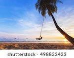 Young happy woman relaxing on a swing attached to a palm tree on a paradise beach at sunset while on vacation in a tropical country - stock photo