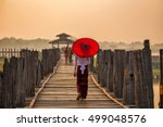 Burmese girl holding a red umbrella walking on U Bein Bridge in the morning in Mandalay, Myanmar.