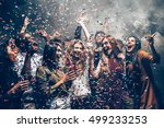 Stock photo fun in motion group of beautiful young people throwing colorful confetti while dancing and looking 499233253