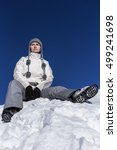 Small photo of Young woman sitting on top of a snowy mountain admiring the view