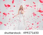 Stock photo fashionable blonde beauty among falling rose petals 499271650