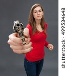 Small photo of beautiful arrogant young woman provoking with an oversized hand gun in the foreground, threatening and accusing with a firearm