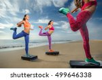 Small photo of fitness, training, aerobics and people concept - group of girls working out with steppers on the beach (Focus on front female body)