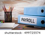 Small photo of Payroll, Office Binder on Wooden Desk. On the table colored pencils, pen, notebook paper