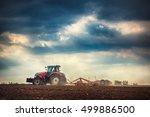 Farmer In Tractor Preparing...