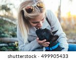 Stock photo young blond woman enjoying with her french bulldog puppy in sunny day selective focus 499905433