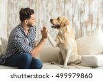 Stock photo happy guy sitting on a sofa and looking at dog 499979860