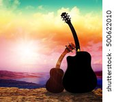 Small photo of Guitar and Ukulele bowed shoulders, facing the sunset.