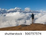Small photo of Solitude landscape in high Himalayan mountains in Nepal. Single traveler standing on the edge of the cliff looking to the distant snowy mountain peaks. Beautiful mountains solitude landscape.