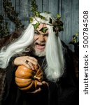 Small photo of Senister old white-haired warlock with wreath of ivy compresses pumpkin in wooden house