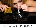 Small photo of Addict drug sniffing through the dollar. On a black background.