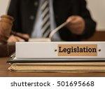 Small photo of legislation document folder with judge or lawyer studying legal. Concepts of law, legislative, legislate.